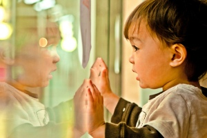 small child looking at himself in a store window